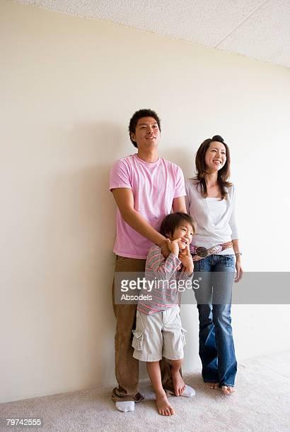 Parents with son (6-7) standing, portrait