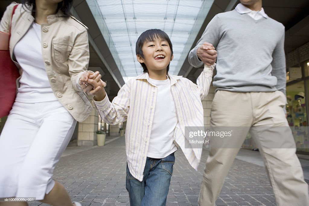 Parents with son (6-7) walking in shopping mall : Stockfoto