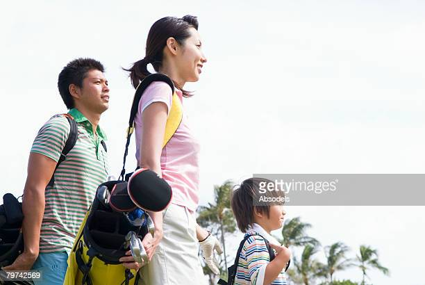 Parents with son (6-7) walking on golf course