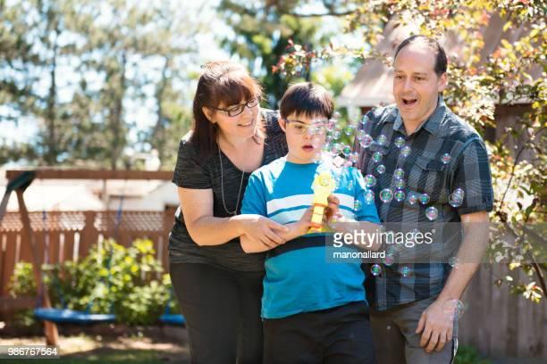 Eltern mit ihrem autistischen und Down-Syndrom Kind im Alltag