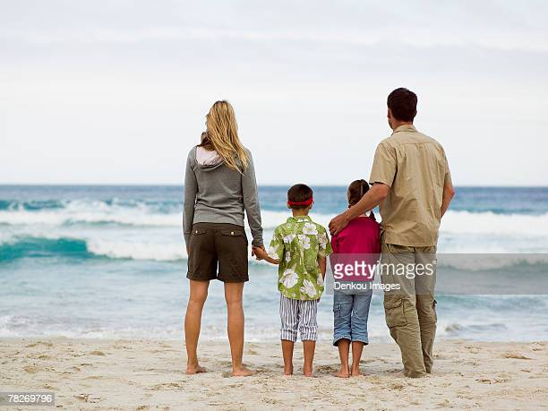 parents with their children on the beach. - beige shorts stock photos and pictures