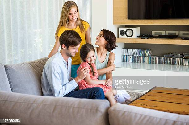 Parents with their children sitting in a living room