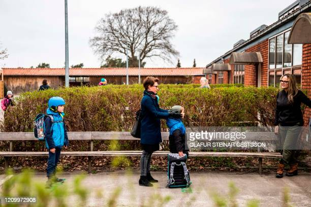 Parents with their children stand in queue waiting to get inside Stengaard School north of Copenhagen, Denmark, on April 15 after the new coronavirus...