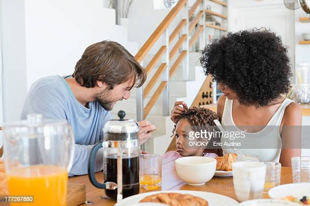 Parents with their daughter at a dining table