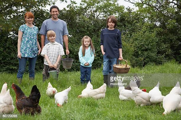Parents with three children (5-9) feeding hens in garden portrait