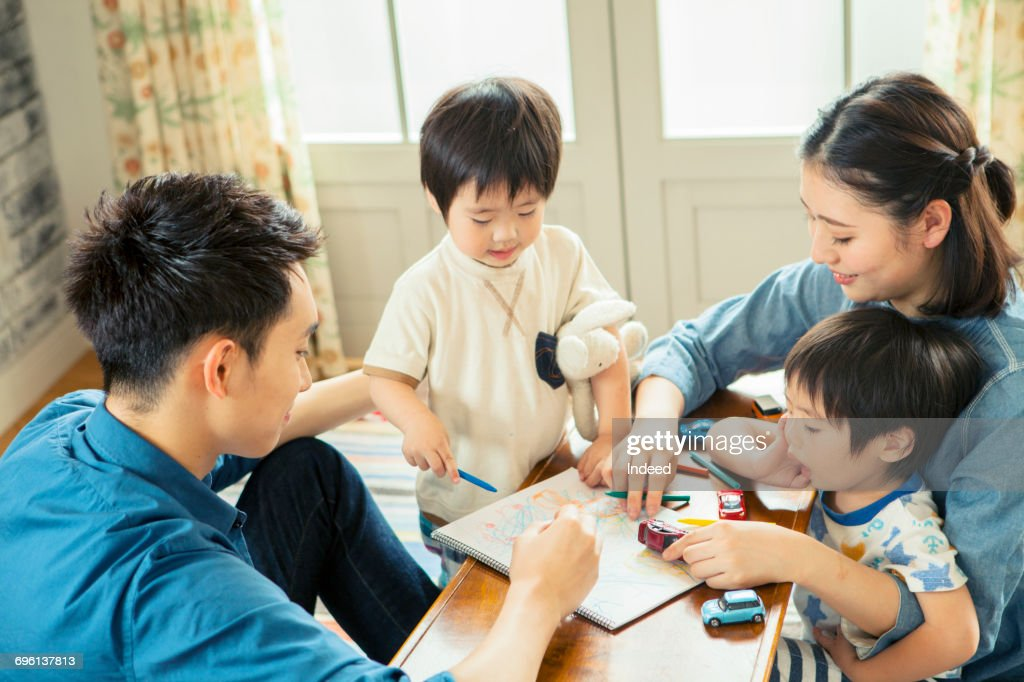 Parents with two boys drawing on sketch pat at table : ストックフォト