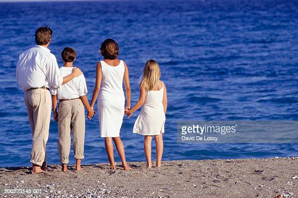 Parents with two children (10-11) (14-15) looking at sea ,rear view