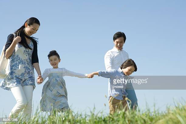 Parents with two children walking on grass