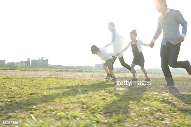 Parents with two kids holding hands and running