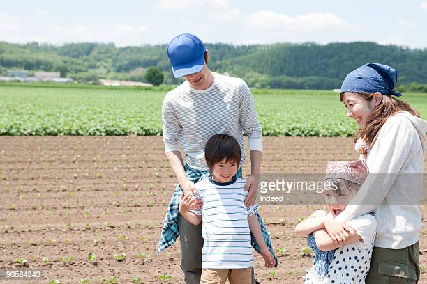 Parents with two kids in vegetable field