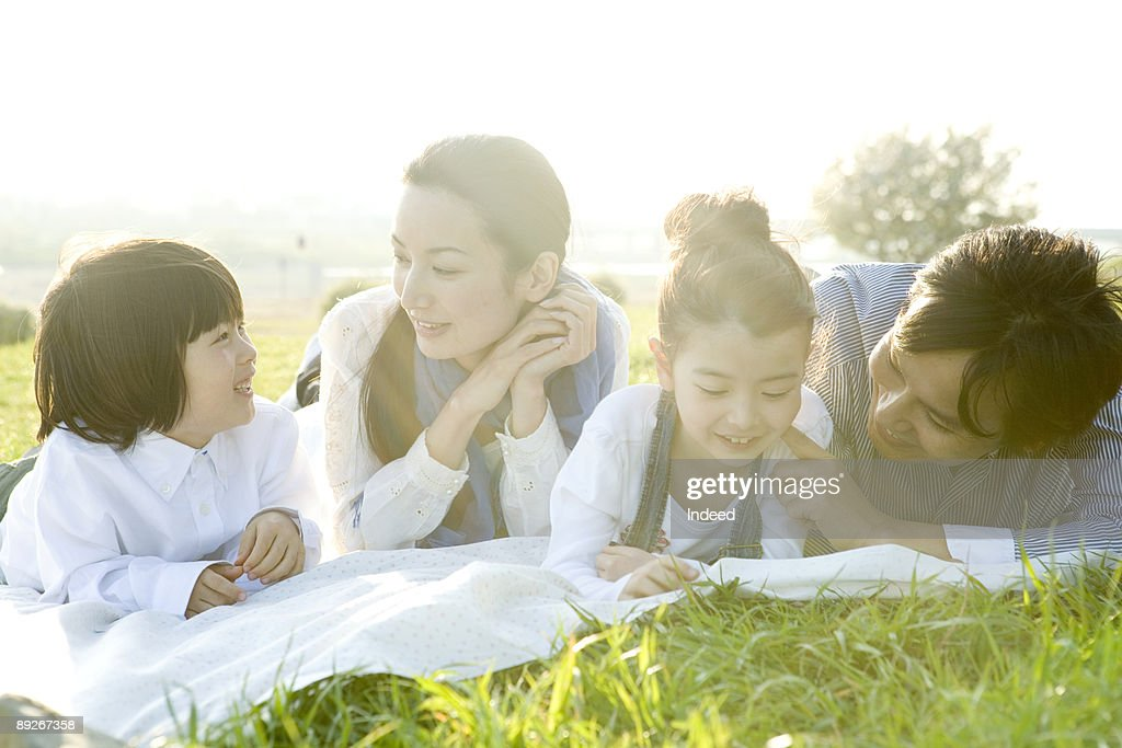Parents with two kids lying relaxing on mat  : Stock Photo