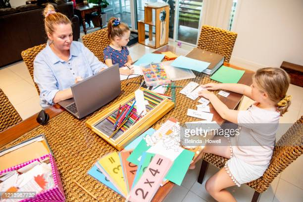 parents working from home helping young children with school work - homeschool stock pictures, royalty-free photos & images