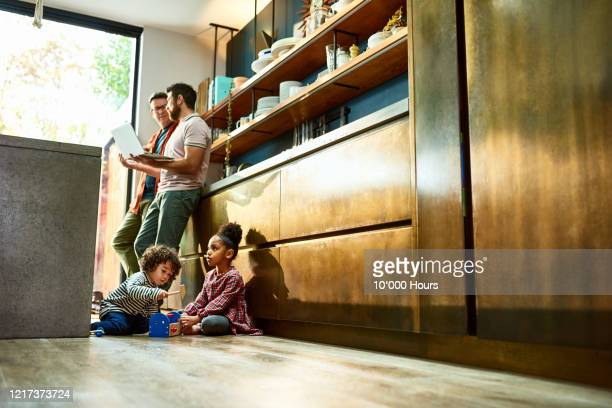 parents working with children playing on floor during lockdown - couple stock pictures, royalty-free photos & images