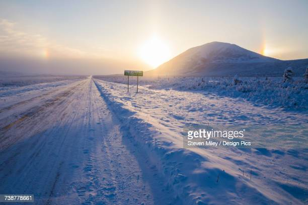 parhelia (sundogs) surround the sun and donnelly dome in this winter view of the richardson highway south of delta junction - miley fotografías e imágenes de stock