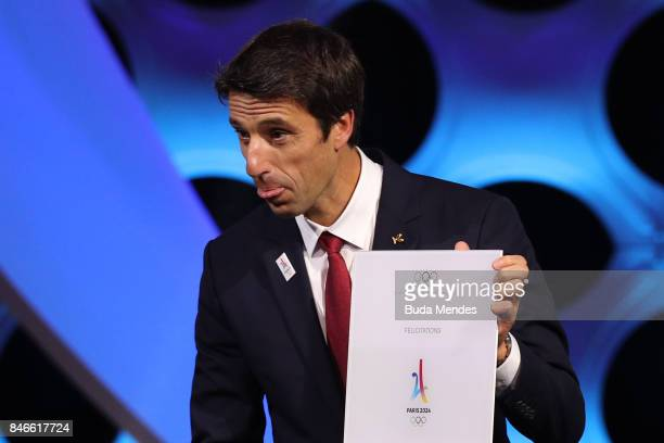 Paris 2024 Bid CoChair and 3time Olympic Champion Tony Estanguet shows and IOC document during a joint press conference between IOC Paris 2024 and...