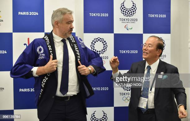 Paris 2024 Director General Etienne Thobois wears a traditional Japanese happi coat presented by Tokyo 2020 CEO Toshiro Muto after a signing ceremony...