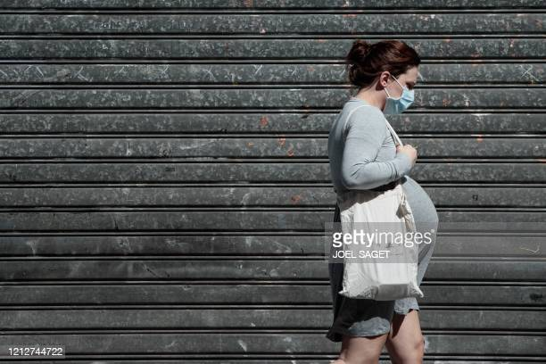 A pregnant woman walk in the stress in Paris on May 12, 2020 . JOEL SAGET / AFP .. .