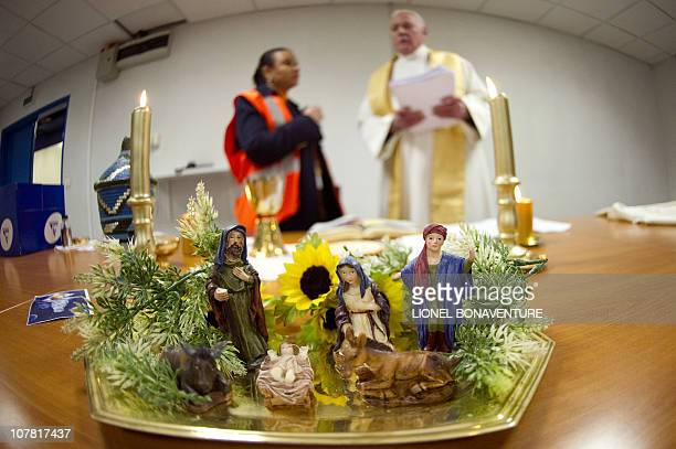 Paris Airports' chaplain Father Francis Truptil starts celebrating mass near a manger on Christmas Eve on December 24 2010 at the RoissyenFrance...