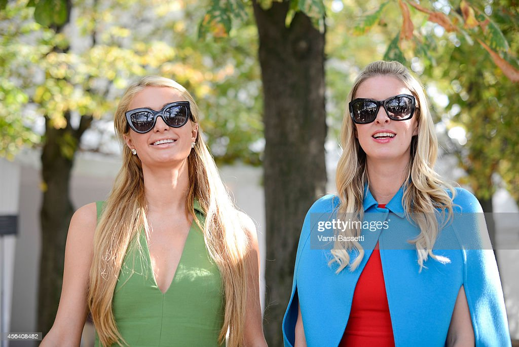Paris (L) and Niki (R) Hilton pose wearing Valentino after the Valentino show on September 30, 2014 in Paris, France.