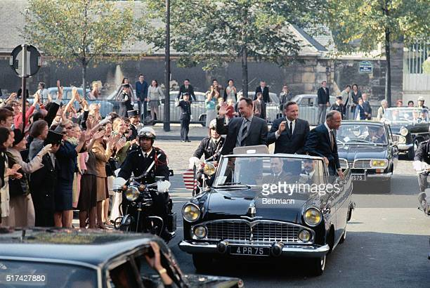 Apollo 11 astronauts wave to crowds as they ride in motorcade through the Paris streets as part of their global good will tour Left to right Michael...