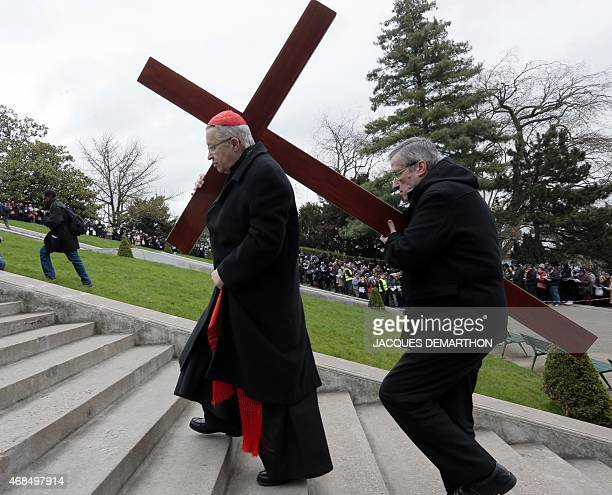 Paris archbishop Andre VingtTrois carries a cross as he heads for Montmartre's basilica during a Good Friday procession to commemorate the death of...