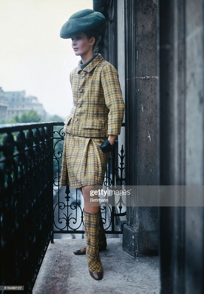 Casual Shape. While come Paris designers dropped their hemlines well below the knee, Couturier designed his skirts to show the kneecap. This bright yellow, green and brown plaid wool suit notes the designer's reverse decision on the hemline theme. Its semi-fitted jacket tops a skirt with two inverted pleats at front and back. Completing the ensemble the Couturier adds matching calf-high boots.