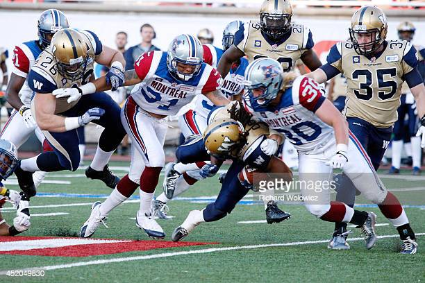 Paris Cotton of the Winnipeg Blue Bombers is tackled by James Tuck of the Montreal Alouettes during the CFL game at Percival Molson Stadium on July...