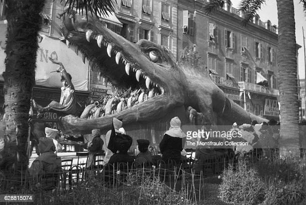 Paris crowds gathered at a Feast of Fools type parade with a very large ferocious dragonlike model creature with a caricature comical clown in the...