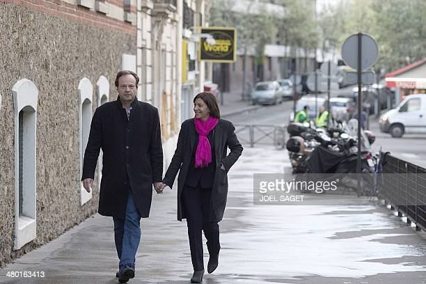 Paris' Deputy Mayor and French Socialist party candidate for the Paris municipal elections Anne Hidalgo walks with her husband JeanMarc Germain after...