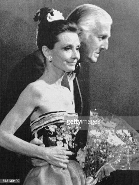 Paris fashion designer Hubert De Givenchy is shown with American actress Audrey Hepburn as each responds to applauding audience at final stage of the...