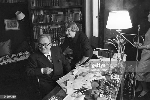 Paris February 5 Marcel Achard author of the play 'potato' with Sophie Daumier sitting behind his desk covered with newspaper articles