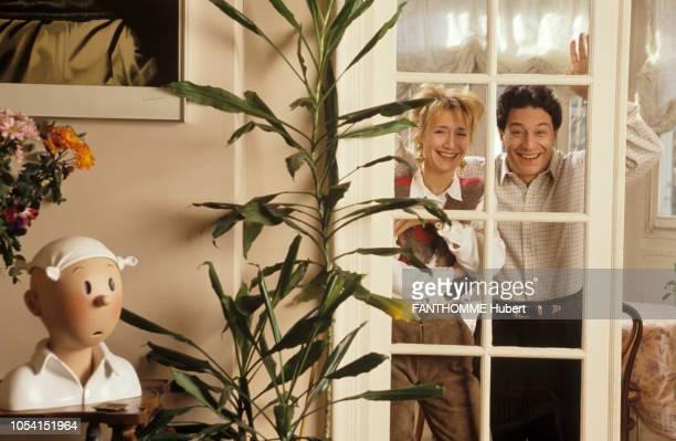 Paris France 18 janvier 1991 Les acteurs Christian CLAVIER et MarieAnne CHAZEL dans leur appartement Le couple riant au travers d'une porte vitrée A...
