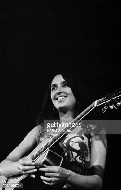 Joan BAEZ vedette du folksong américain a choisi le Palais de la Mutualité pour son unique récital en Europe Ici en plan taille jouant de la guitare...