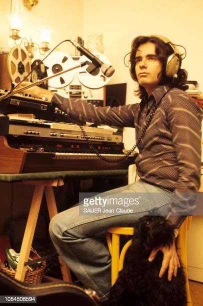 Paris France 1er février 1976 Le chanteur Nicolas PEYRAC chez lui à Paris Ici à son clavier et deux magnétophones à bande un casque audio sur les...