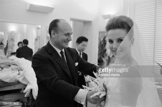 Paris France 24 janvier 1963 Présentation de la collection du grand couturier BALMAIN Ici le couturier ajustant avec le sourire une robe de mariée...