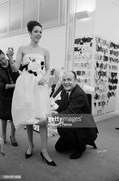 Paris France 24 janvier 1963 Présentation de la collection du grand couturier BALMAIN Le couturier travaillant l'ourlet d'une robe portée par un...