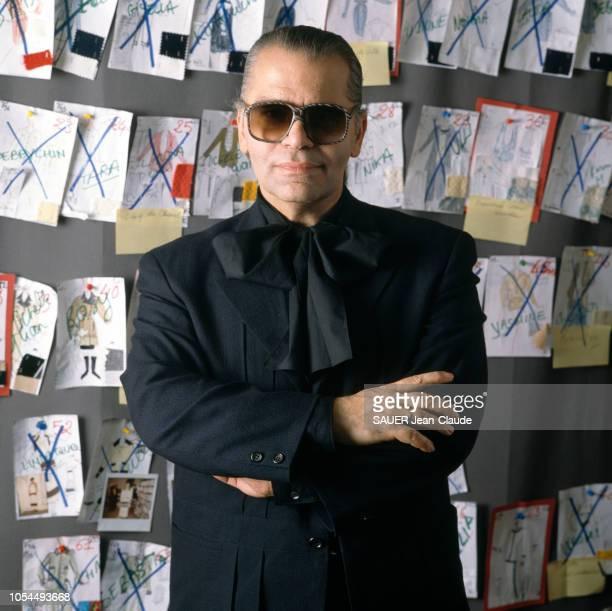 Paris France 24 octobre 1988 Le styliste allemand Karl LAGERFELD pose dans son bureau avec des lunettes de soleil Derrière lui des croquis de mode...