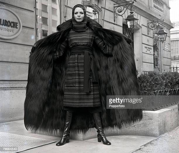 Paris, France, 31st July 1970, A model wearing a large tweed cape with monkey skin fur, worn over a red and black tunic dress by French designer Guy...