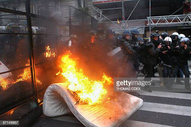 A mattress burns in front of a fence protecting riot policemen from demonstrators during a rally against the First Employment Contract 21 March 2006...