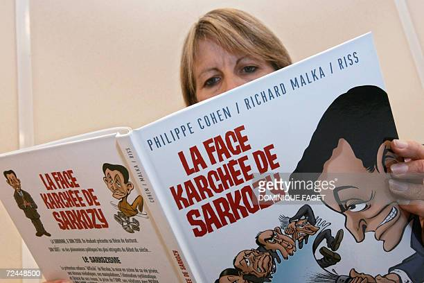 A woman reads a comic book 'La Face Karchee de Sarkozy' by Philippe Cohen Richard Malka and Riss which traces the life and times of French...