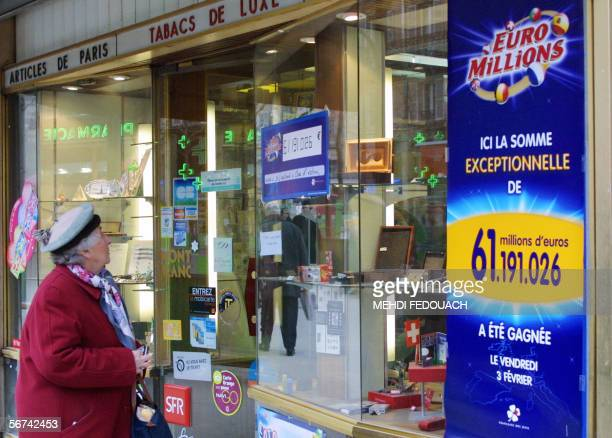 An old woman looks at a board announcing the amount of the prize won by one of the three EuroMillions jackpot lucky winners who validated his ticket...