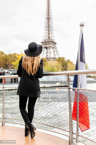Paris, France, back view of tourist taking a cruise on Seine River looking at Eiffel Tower