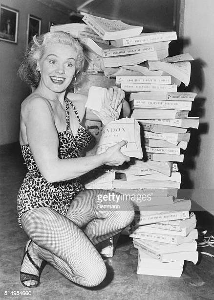 Blond British strong woman Joan Rhodes keeps in trim for a Paris appearance by ripping a set of London phone books in half Those are pretty biceps...