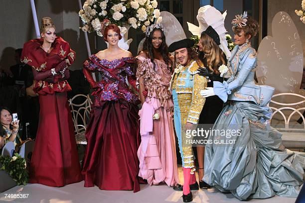 British designer John Galliano poses with Canadian model Linda Evangelista British model Naomi Campbell Brazilian model Gisele Bundchen at the end of...
