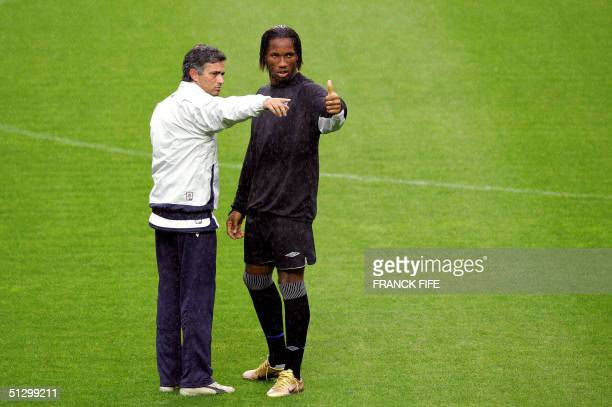Chelsea's Ivorian forward Didier Drogba speaks with Portuguese coach Jose Mourinho after a training session 13 September 2004 at the Parc des Princes...