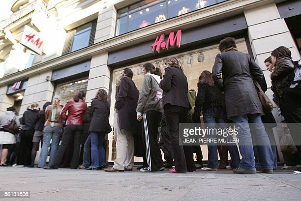 Customers queue 10 November 2005 in front of Hennes and Mauritz outlet for the launch of British designer Stella McCartney's fashion line at one of...