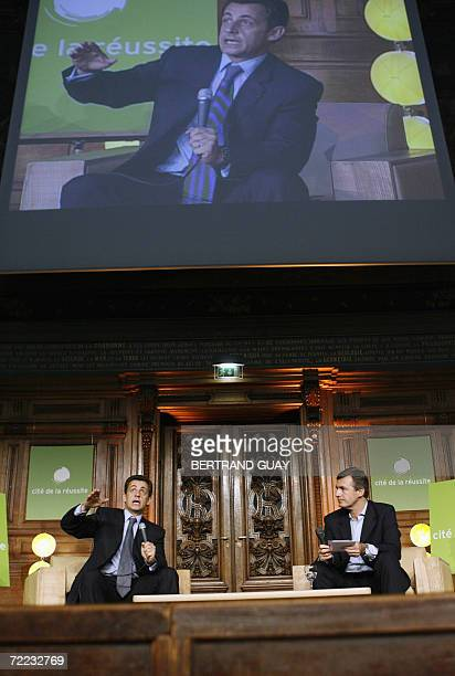 French Interior minister Nicolas Sarkozy answers a question next to journalist Nicolas Beytout during a debate organized by the Cite de la Reussite...