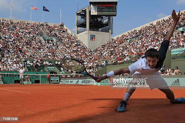French player Olivier Patience hits a forehand shot to Serbian player Novak Djokovic during their French Tennis Open third round match at Roland...
