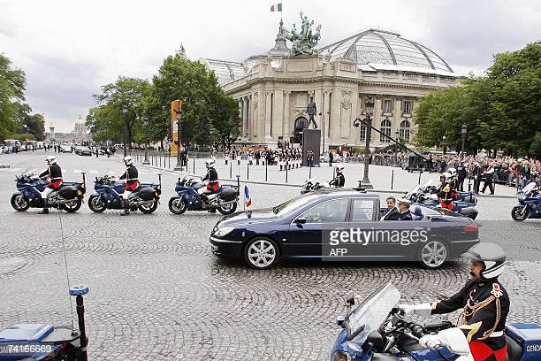 French President Nicolas Sarkozy waves from his car 16 May 2007 as he drives down the ChampsElysees avenue in Paris in an opentop car escorted by the...