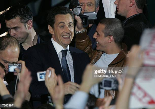 French rightwing presidential candidate Nicolas Sarkozy chats with French singer Faudel at the end of a campaign meeting at the 'Zenith' in Paris 18...
